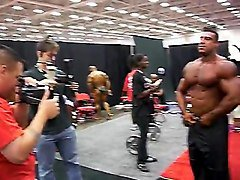 str8 greek bodybuilder flexing in backstage