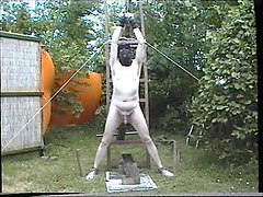 chained naked male slave gets his cock and balls roasted