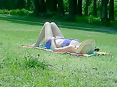 Mature woman sunbathing in public park